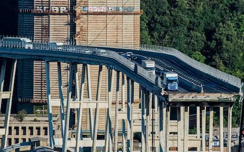 <span>Cars and trucks are left on a section of the collapsed Morandi highway bridge in Genoa</span> <span>Credit: Nicola Marfisi/AP </span>