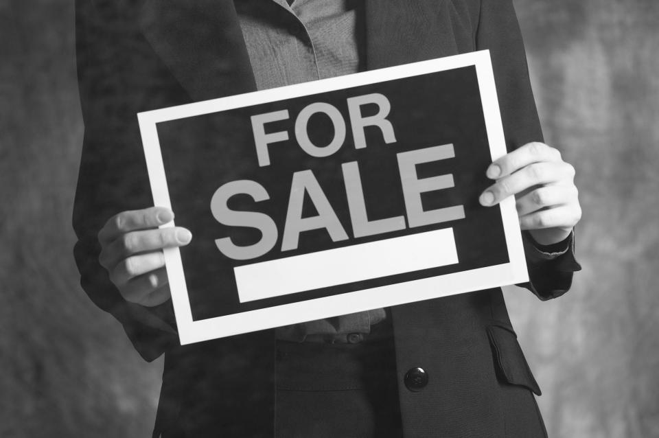 A businessman holding up a for sale sign.