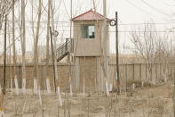 A security person watches from a guard tower around a detention facility in Yarkent County in northwestern China's Xinjiang Uyghur Autonomous Region on March 21, 2021. Four years after Beijing's brutal crackdown on largely Muslim minorities native to Xinjiang, Chinese authorities are dialing back the region's high-tech police state and stepping up tourism. But even as a sense of normality returns, fear remains, hidden but pervasive. (AP Photo/Ng Han Guan)
