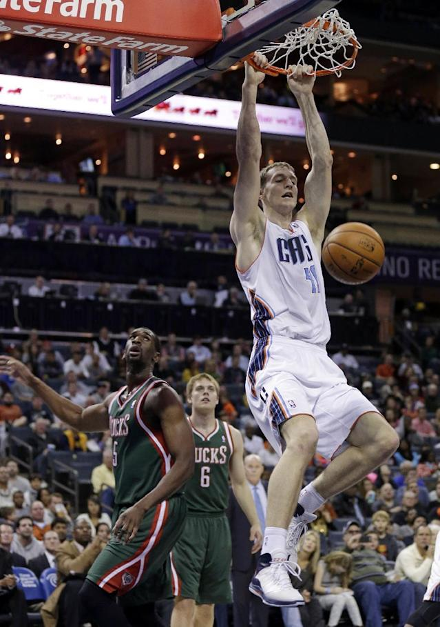 Charlotte Bobcats' Cody Zeller, right, dunks as Milwaukee Bucks' Ekpe Udoh (5) looks on during the first half of an NBA basketball game in Charlotte, N.C., Friday, Nov. 29, 2013. (AP Photo/Chuck Burton)