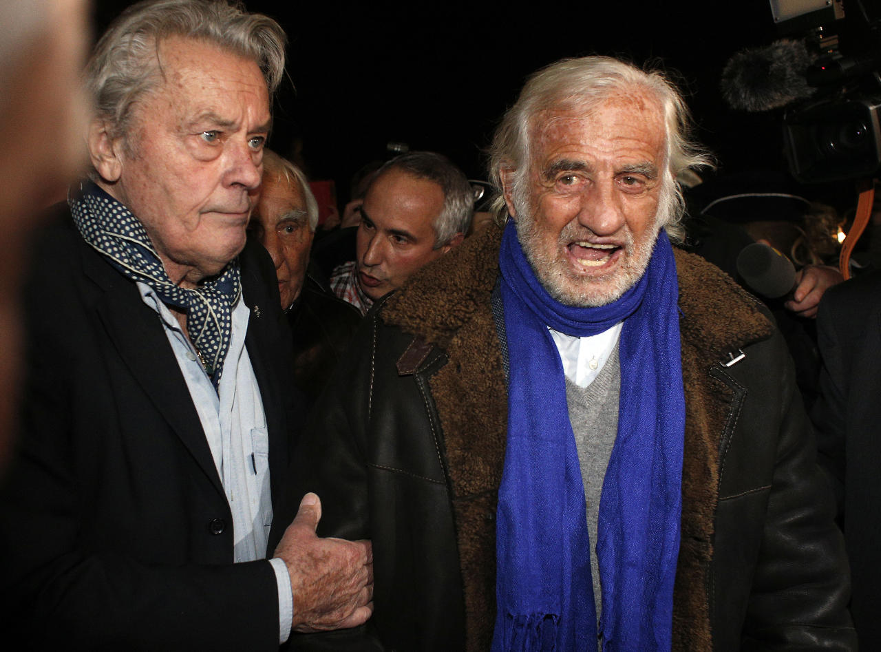 French actors Alain Delon, left, and Jean Paul Belmondo, center, right, arrive for the inauguration of a giant Ferris wheel, in Paris, Friday, Nov. 17, 2017. (AP Photo/Thibault Camus)