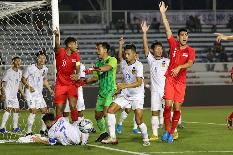 Players react after the call of the referee during the match between Singapore and Laos for the first round of the mens football of the 30th South East Asian Games held at the Rizal Memorial Stadium in Manila on November 26, 2019. (Photo by George Calvelo/NurPhoto via Getty Images)