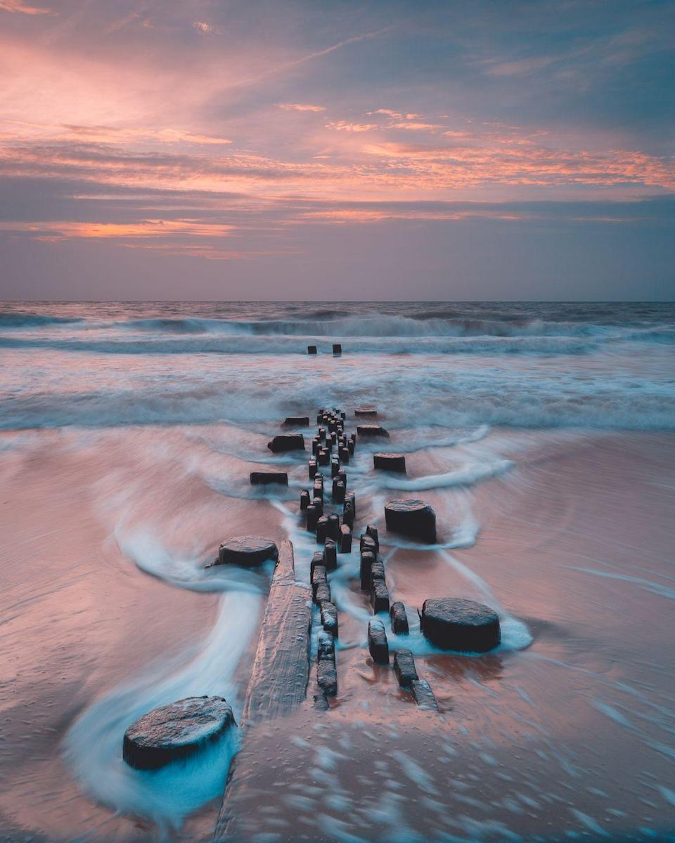 <p>Cloudy skies don't take away from the beauty of sunset at Rehoboth Beach in Delaware.</p>
