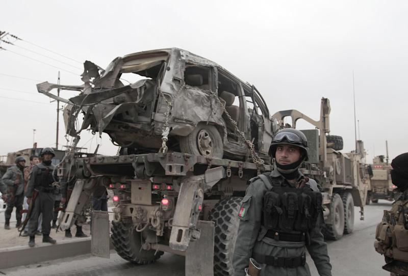 A U.S. military wrecker carries away a vehicle that was destroyed in a suicide car bomb attack on the Jalalabad-Kabul road in Kabul, Afghanistan, Friday, Dec. 27, 2013. The U.S.-led coalition in Afghanistan says several service members were killed Friday when a suicide car bomber attacked their convoy in an eastern district of the capital, Kabul. (AP Photo/Rahmat Gul)