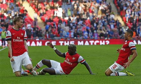 Arsenal's Per Mertesacker (L) celebrates his goal against Wigan Athletic with teammates Bacary Sagna (C) and Alex Oxlade-Chamberlain during their English FA Cup semi-final soccer match at Wembley Stadium in London April 12, 2014. REUTERS/Eddie Keogh