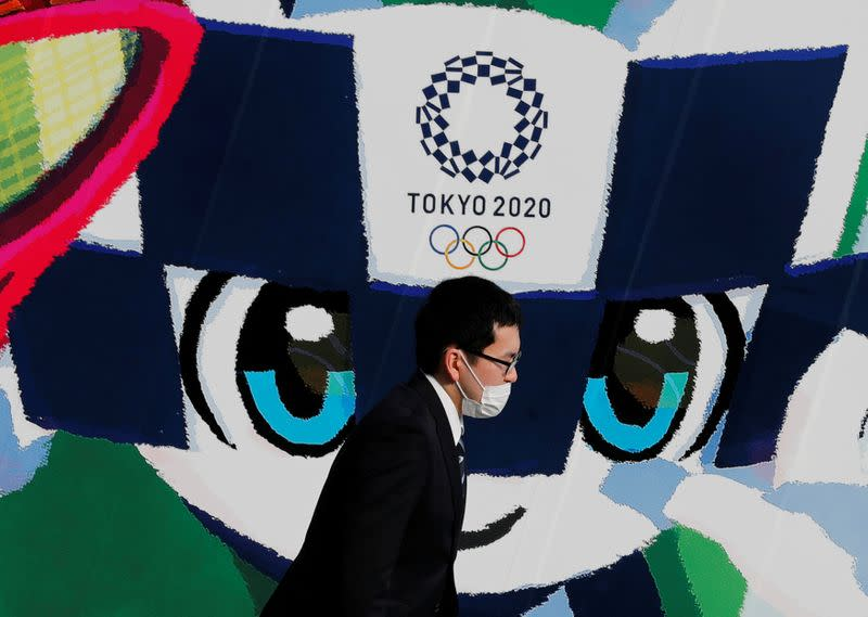 FILE PHOTO: A man wearing a protective mask walks past a large poster featuring Tokyo 2020 Olympic Games mascot Miraitowa amid the coronavirus disease (COVID-19) outbreak in Tokyo