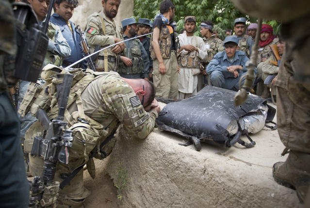 <p>U.S. Army Captain Michael Kelvington, commander of the Battle company, 1-508 Parachute Infantry battalion, 4th Brigade Combat Team, 82nd Airborne Division, bows next to remains of Gulam Dostager, a member of Afghan Local Police who was killed in the blast of an Improvised Explosive Device (IED) during the joint Tor Janda (Black Flag in Pashtu) operation, in Zahri district of Kandahar province, southern Afghanistan on May 25, 2012. (Photo: Shamil Zhumatov/Reuters) </p>