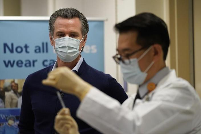 ADVANCE FOR RELEASE MARCH 14, 2021, AND THEREAFTER - File - In this Dec. 14, 2020, file photo, California Gov. Gavin Newsom watches as the Pfizer-BioNTech COVID-19 vaccine is prepared by Director of Inpatient Pharmacy David Cheng at Kaiser Permanente Los Angeles Medical Center in Los Angeles. Some of the nation's governors' offices routinely block access to public records to keep the public in the dark about key decisions involving the coronavirus pandemic. In California, Newsom's office last year denied an AP request for communications showing how the Democratic governor made decisions related to the virus outbreak. (AP Photo/Jae C. Hong, File)