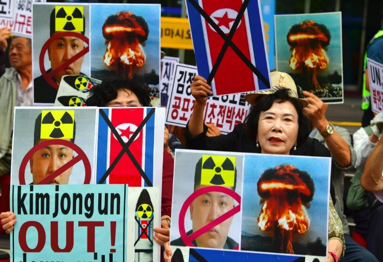 South Korean conservative activists hold placards showing the portrait of North Korean leader Kim Jong-Un during a protest denouncing North Korea's nuclear test in Seoul on September 10, 2016
