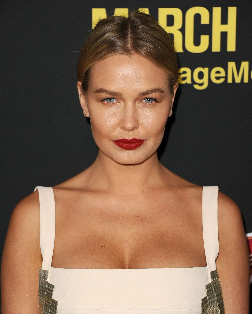 Lara Worthington poses at premiere event in white gown