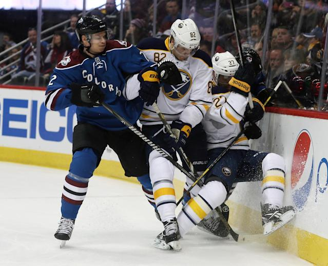 Colorado Avalanche defenseman Nick Holden, left, battles for control of the puck with Buffalo Sabres left wing Marcus Foligno, center, and right wing Matt D'Agostini in the first period of an NHL hockey game in Denver, Saturday, Feb. 1, 2014. (AP Photo/David Zalubowski)