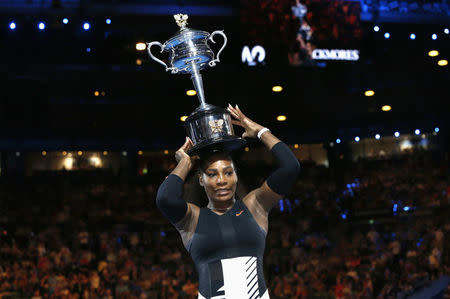 Serena Williams places her trophy on her head after winning her Women's singles final match against Venus Williams. REUTERS/Issei Kato
