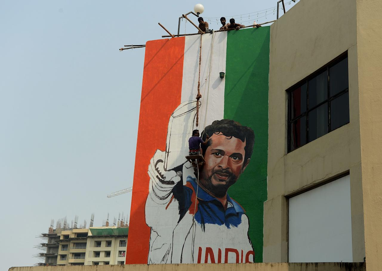 To go with Cricket-IND-Tendulkar,FOCUS by Kuldip LAL  Indian artist Ranjit Dahiya works on a mural of cricketer Sachin Tendulkar on the wall of a sports club building in Mumbai on November 8, 2013. Sachin Tendulkar is set for an emotional farewell when he plays his 200th and final Test at home in Mumbai from November 14, exactly 24 years after he began his record-breaking career.  AFP PHOTO/ PUNIT PARANJPE        (Photo credit should read PUNIT PARANJPE/AFP/Getty Images)