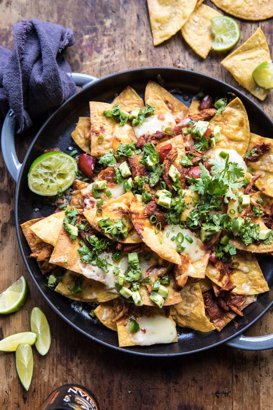 "<p>These decked-out nachos are layered with an enchilada sauce, two different cheeses, and an avocado salsa. It doesn't get any tastier than this!</p><p><strong>Get the recipe at <a href=""https://www.halfbakedharvest.com/chipotle-braised-chicken-nachos/"" rel=""nofollow noopener"" target=""_blank"" data-ylk=""slk:Half Baked Harvest"" class=""link rapid-noclick-resp"">Half Baked Harvest</a>.</strong></p>"