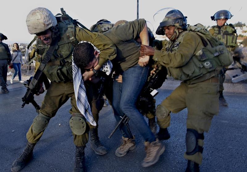 A Palestinian activist is detained by Israeli soldiers during a protest against the Prawer Plan to resettle Israel's Palestinian Bedouin minority from their villages in the Negev Desert, near the Israeli settlement of Bet El, north of the West Bank city of Ramallah, Saturday, Nov. 30, 2013. (AP Photo/Majdi Mohammed)