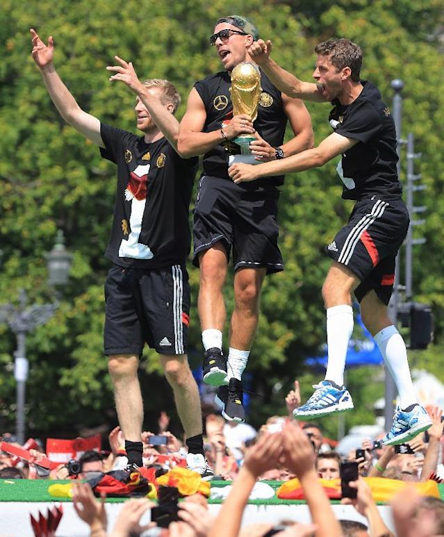 "German national soccer players from left: Per Mertesacker , Lukas Podolski and Thomas Mueller celebrate near Brandenburg Gate in Berlin, Tuesday July 15, 2014. Germany's World Cup winners shared their fourth title with hundreds of thousands of fans by parading the trophy through cheering throngs to celebrate at the Brandenburg Gate on Tuesday. An estimated 400,000 people packed the ""fan mile"" in front of the Berlin landmark to welcome home coach Joachim Loew's team and the trophy which returned to Germany for the first time in 24 years. (AP Photo/dpa, JensWolf)"