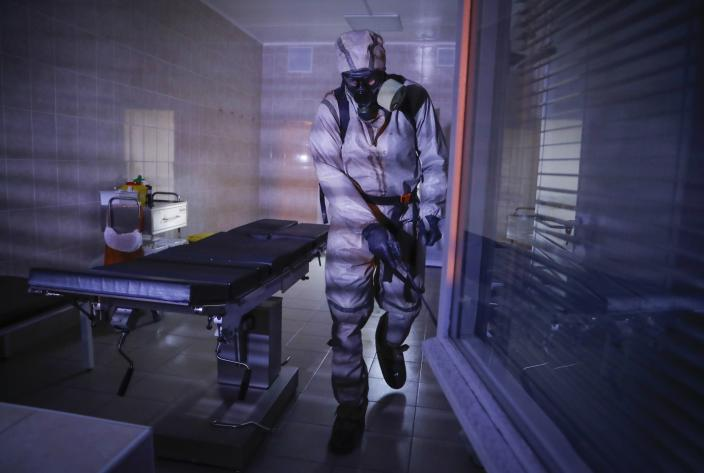 FILE In this file photo taken on Tuesday, May 5, 2020, a serviceman of Belarus Ministry of Defence wearing protective gear disinfects a local hospital in Minsk, Belarus. The 9.5-million Belarus has reported more than 68,500 infections, including 580 deaths, but critics have accused the authorities of manipulating statistics to hide the real number of deaths. (AP Photo/Sergei Grits)