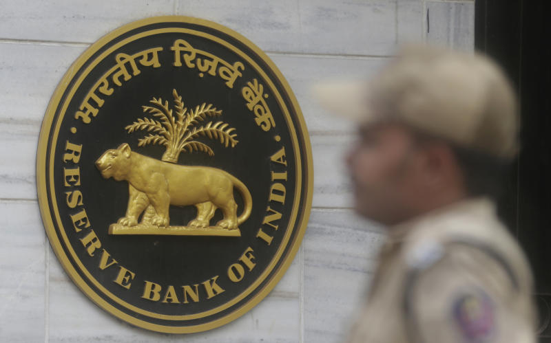 FILE - In this Dec. 6, 2017, file photo, an Indian policeman stands guard outside the headquarters of Reserve Bank of India (RBI) in Mumbai, India. India's central bank has cut its key interest rate by a quarter of a percentage point to 5.75% from 6% with immediate effect to fortify the economy as consumer spending and corporate investment falter, according to a bimonthly review of the economy released on Thursday, June 6, 2019. (AP Photo/Rafiq Maqbool, File)