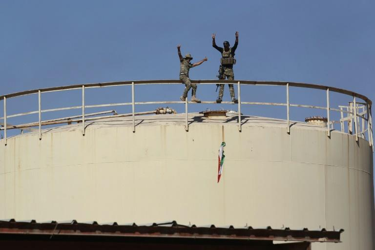 Iraqi government forces remove a Kurdish flag from the Bai Hassan oil field west of Kirkuk after seizing the installation from Kurdish forces on October 17, 2017 in a blow to Kurdish hopes for independence