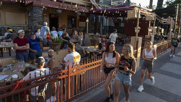 PHOTO: Pedestrians walk past customers sitting outside at a bar in Tucson, Arizona, U.S., on Monday, May 11, 2020. (Cheney Orr/Bloomberg via Getty Images)