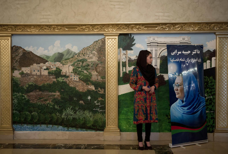 """An Afghan female election worker and supporter of Habiba Sarabi, pictured on the placard, one of presidential candidate Zalmai Rassoul's picks for vice president, waits for women to arrive for a meeting to discuss the upcoming elections in a hotel in Kabul, Afghanistan, Wednesday, March 26, 2014. A large number of women, including women parliamentarians attended the meeting saying they were there in solidarity with Sarabi, one of only three women chosen as running mates by presidential candidates, who can choose two vice presidents. The banner reads, """"Habiba Sarabi - one woman who can stand up for any situation."""" (AP Photo/Anja Niedringhaus)"""