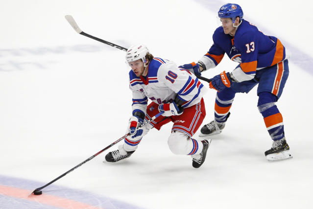 New York Islanders center Mathew Barzal (13) tries to get the puck from New York Rangers left wing Artemi Panarin (10) as Panarin looks to pass in the third period of an NHL hockey game, Tuesday, Feb. 25, 2020, in Uniondale, N.Y. The Rangers defeated the Islanders 4-3 in overtime. (AP Photo/Kathy Willens)