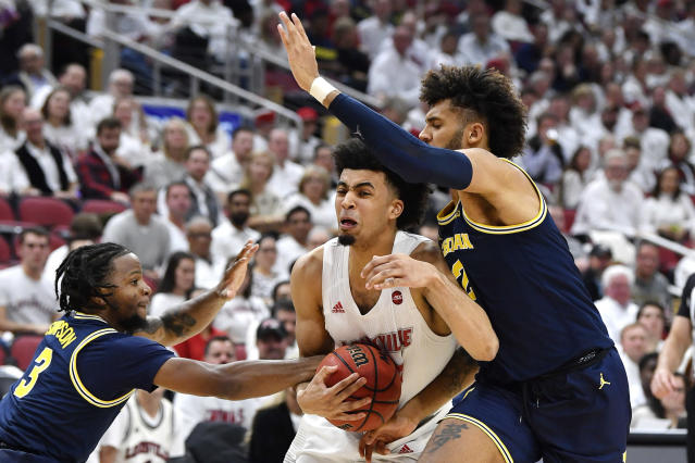 Louisville forward Jordan Nwora (33) is fouled by Michigan guard Zavier Simpson (3), left, as forward Isaiah Livers (2) defends from the right during the second half of an NCAA college basketball game in Louisville, Ky., Tuesday, Dec. 3, 2019. Louisville won 58-43. (AP Photo/Timothy D. Easley)