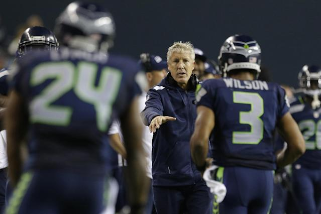 Seattle Seahawks head coach head coach Pete Carroll, center, greets Seahawks' Marshawn Lynch, left, and Russell Wilson (3) after Lynch scored a touchdown against the San Francisco 49ers in the second half of an NFL football game, Sunday, Sept. 15, 2013, in Seattle. (AP Photo/Elaine Thompson)