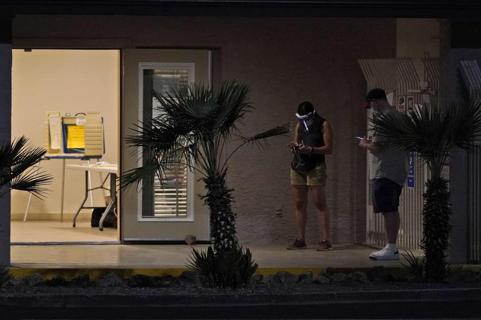 Poll workers check their phones as they wait for voters at a local polling station Tuesday, Nov. 3, 2020 in Tucson, Ariz. (AP Photo/Ross D. Franklin)