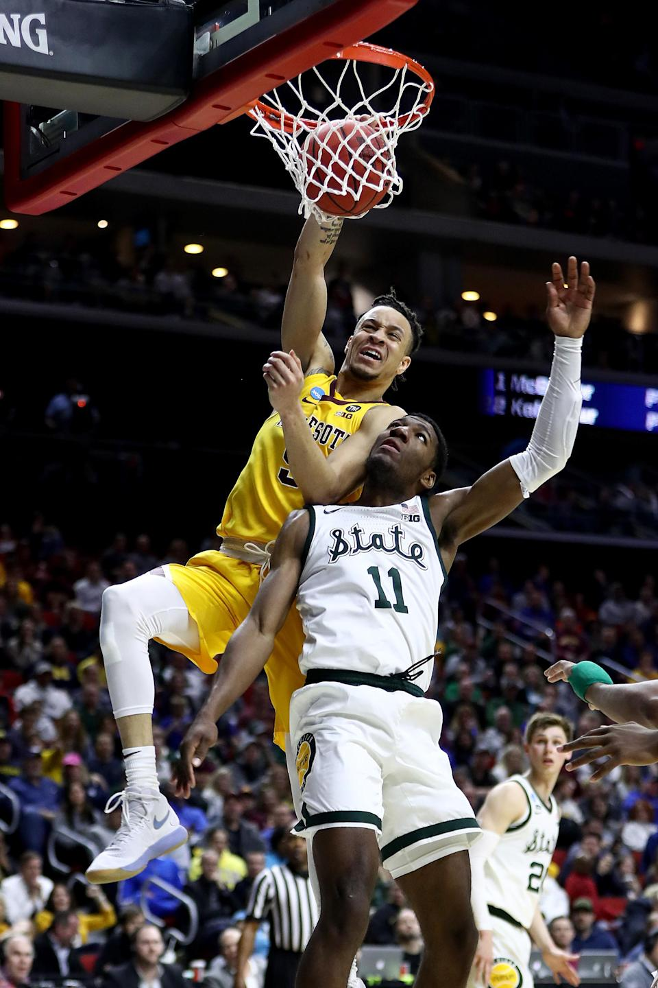 <p>Amir Coffey #5 of the Minnesota Golden Gophers dunks the ball against Aaron Henry #11 of the Michigan State Spartans during the first half in the second round game of the 2019 NCAA Men's Basketball Tournament at Wells Fargo Arena on March 23, 2019 in Des Moines, Iowa. (Photo by Jamie Squire/Getty Images) </p>