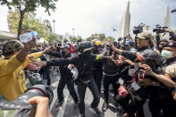 Supporters of the the monarchy, left, and pro-democracy supporters scuffle at a rally near the Democracy Monument in Bangkok, Thailand, Wednesday, Oct. 14, 2020. Thousands of anti-government protesters gathered Wednesday for a rally at Bangkok's Democracy Monument being held on the anniversary of a 1973 popular uprising that led to the ousting of a military dictatorship, amid a heavy police presence and fear of clashes with political opponents. (AP Photo/Wason Wanichakorn)