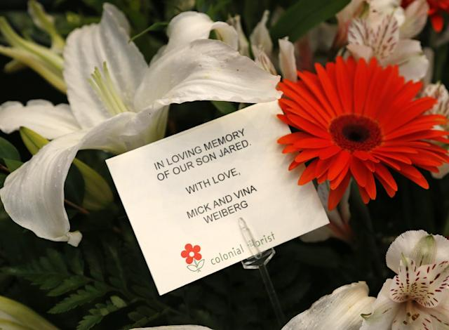 """A card that states """"In loving memory of our son Jared"""" is pictured at the memorial to the the 10 men killed in the Jan. 27, 2001 Oklahoma State plane crash before the start of an NCAA college basketball game between West Virginia and Oklahoma State in Stillwater, Okla., Saturday, Jan. 25, 2014. Jared Weiberg, student assistant, was one of the ten who died. (AP Photo/Sue Ogrocki)"""