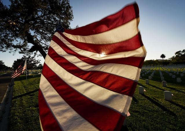 <p>The sun sets over a flag at the Los Angeles National Military Cemetery two days before Memorial Day in Los Angeles, Calif., on May 26, 2018. Memorial Day, which originated after the US Civil War that ended in 1865, is an American holiday honoring the men and women who died while serving in the U.S. military. (Photo: Mark Ralston/AFP/Getty Images) </p>