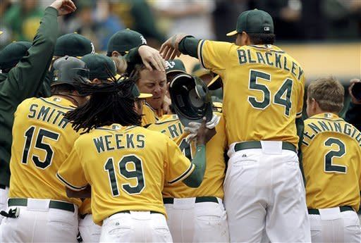 Oakland Athletics players mob Yoenis Cespedes after Cespedes hit a walk-off, three-run home run off Los Angeles Dodgers' Josh Lindblom in the ninth inning of a baseball game, Thursday, June 21, 2012, in Oakland, Calif. The Athletics won 4-1. (AP Photo/Ben Margot)