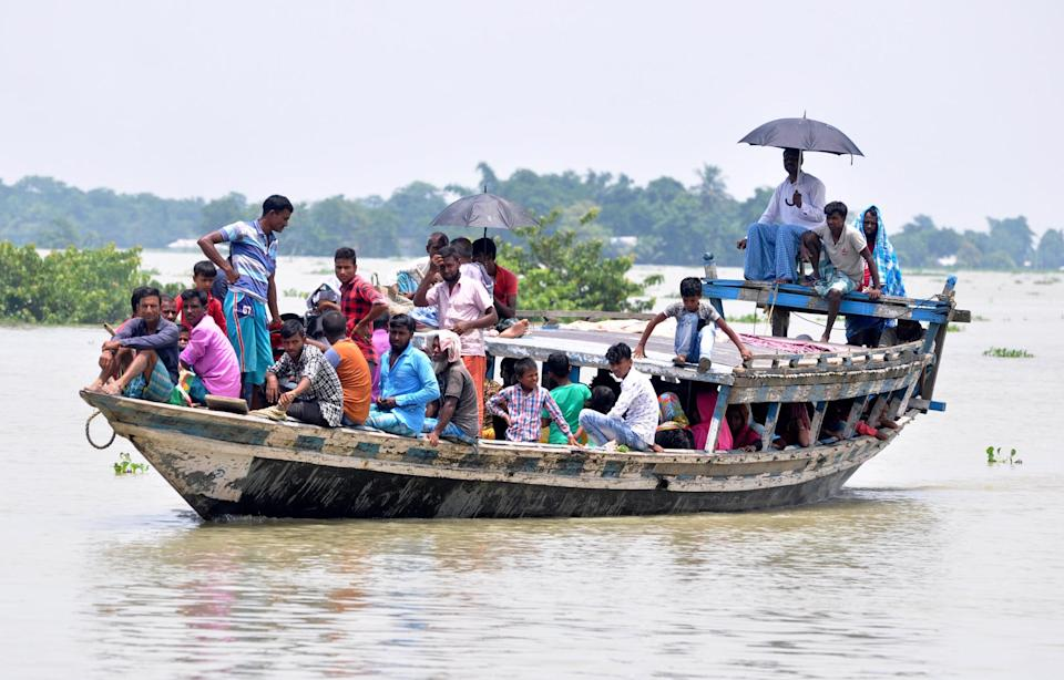 Indian villagers cross a flooded area by a boat, at Jhargaon in Morigaon district of Assam. (Photo credit should read Anuwar Ali Hazarika/Barcroft Media via Getty Images)