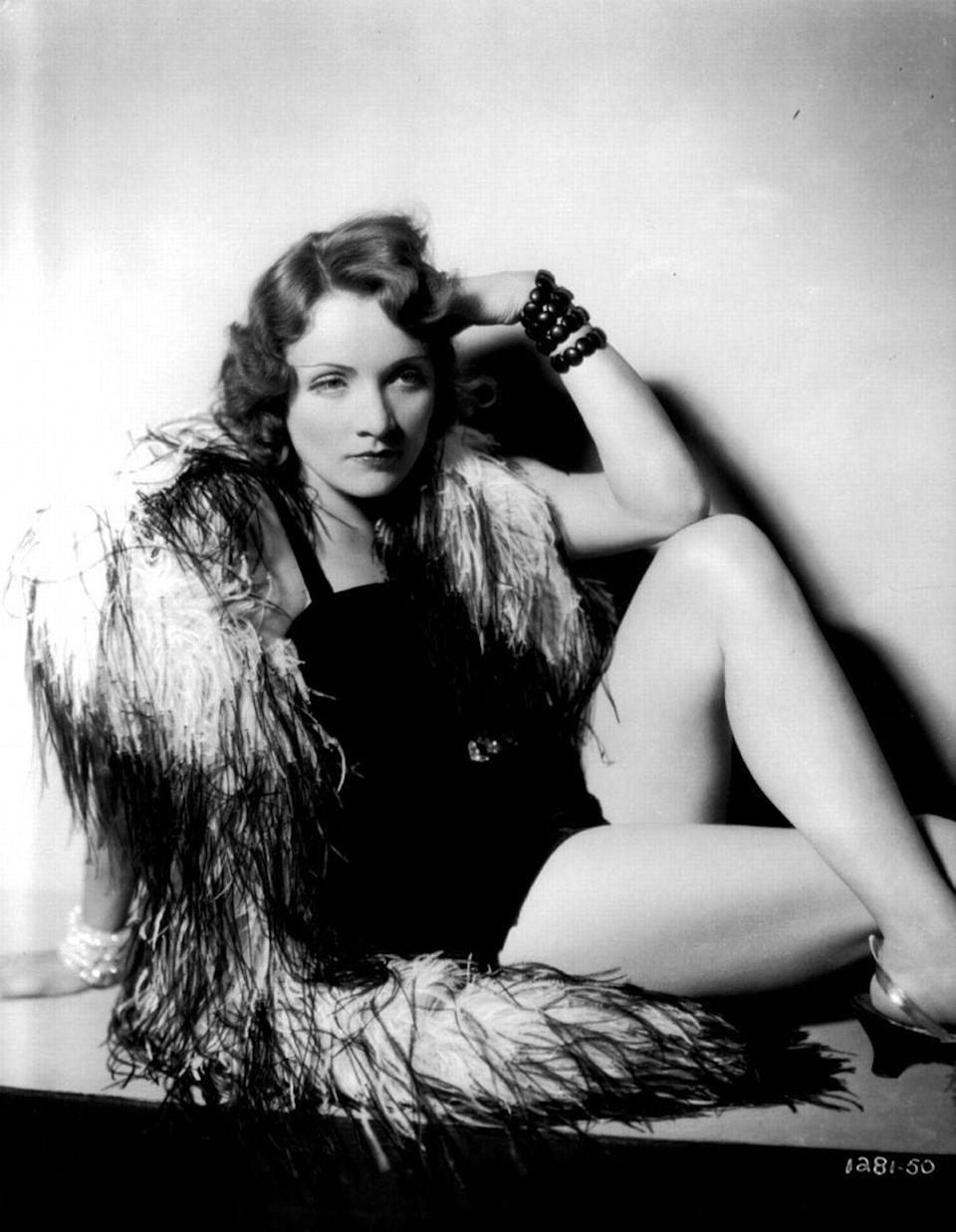 <p>Dietrich, the German-born actress, poses in a scene while filming <em>Morocco </em>and oozes allurement in a black one-piece and feathered wrap. <br></p>