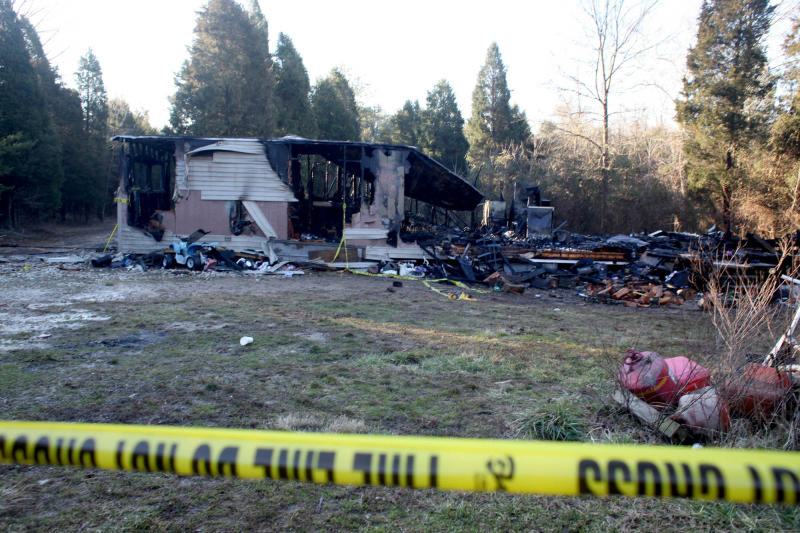 The remains of a mobile home are seen Thursday, Feb. 7, 2013, after an early morning fire claimed the lives of two children and three adults near the rural community of Sulphur in southern Indiana. The residents were relying on a wood stove to heat the home, and authorities suspect that stove likely sparked the fire. (AP Photo/The Courier-Journal, Aaron Borton) NO SALES, NO ARCHIVE, MAGS OUT