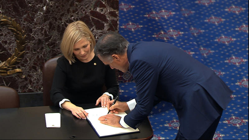 In this image from video, Sen. Mitt Romney, R-Utah, signs the oath book after being sworn in for the impeachment trial of President Donald Trump in the Senate at the U.S. Capitol in Washington, Thursday, Jan. 16, 2020. (Senate Television via AP)