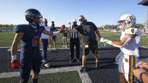 Davis head coach Mitch Arquette, center, fist bumps Herriman's Brock Hollingsworth (5) during the coin toss before the start of a high school football game, on Thursday, Aug. 13, 2020, in Herriman, Utah. Utah is among the states going forward with high school football this fall despite concerns about the ongoing COVID-19 pandemic that led other states and many college football conferences to postpone games in hopes of instead playing in the spring. (AP Photo/Rick Bowmer)
