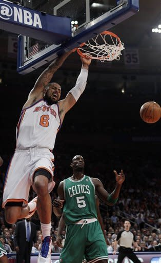New York Knicks' Tyson Chandler (6) dunks the ball as Boston Celtics' Kevin Garnett (5) looks on during the first half of an NBA basketball game Tuesday, April 17, 2012, in New York. (AP Photo/Frank Franklin II)