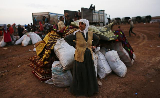 A Syrian Kurdish refugee woman waits for transportation after crossing into Turkey from the Syrian border town Kobani, near the southeastern Turkish town of Suruc in Sanliurfa province October 2, 2014. More than 150,000 refugees have fled Kobani over the past two weeks alone, with a steady exodus continuing. Officials from Turkey's AFAD disaster management agency said some 4,000 crossed on Wednesday, and a similar figure the day before. REUTERS/Murad Sezer (TURKEY - Tags: POLITICS SOCIETY IMMIGRATION CIVIL UNREST CONFLICT)