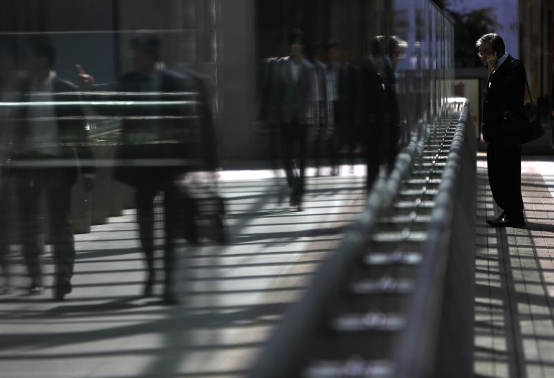 A man uses a mobile phone as pedestrians are reflected in a glass window of a walkway in Tokyo's business district