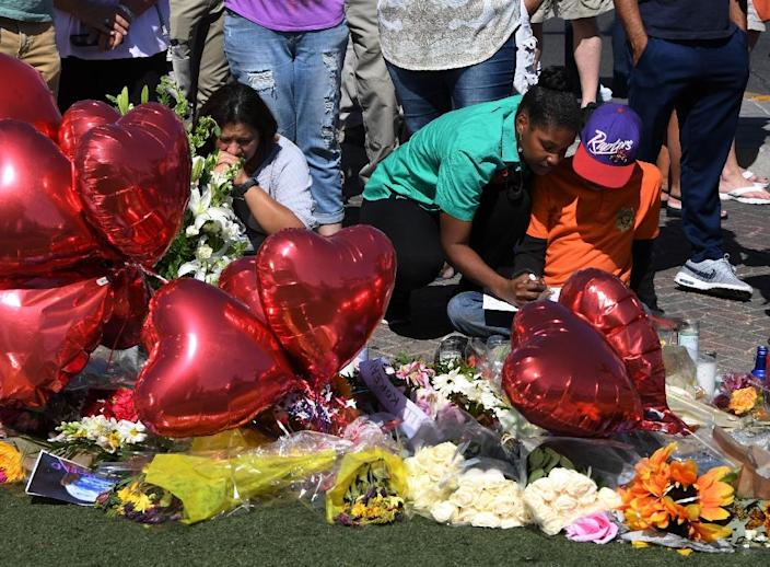 Mourners at a makeshift memorial for victims of the October 1, 2017 attack on concert-goers at a music festival (AFP Photo/Mark RALSTON)