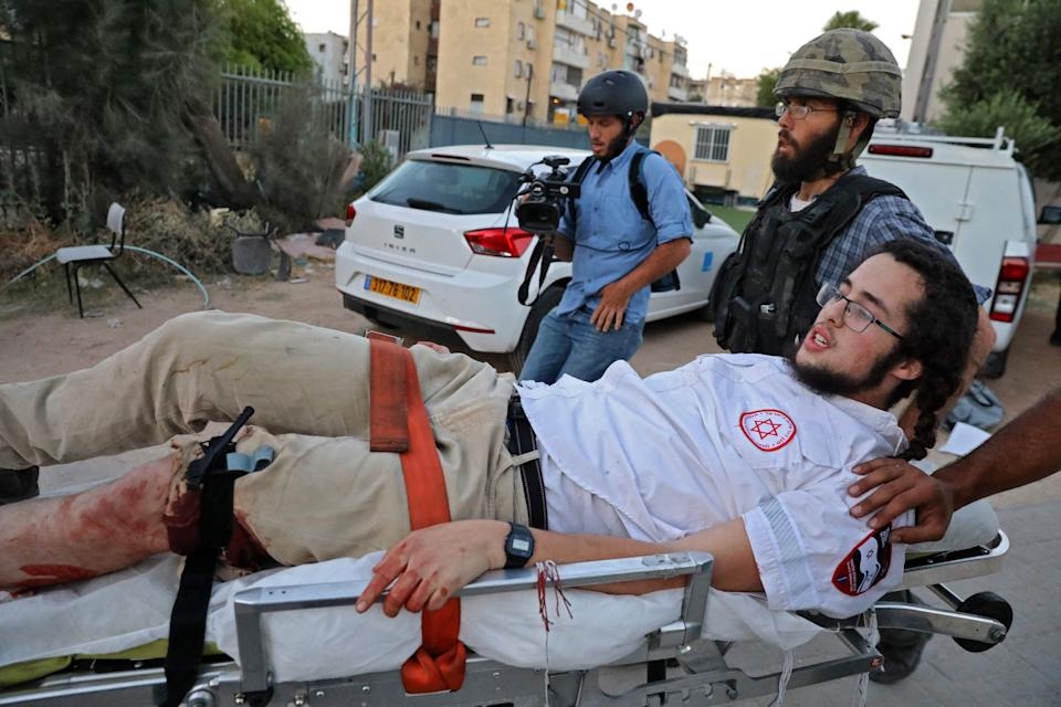 An Israeli far-right extremist is taken away on a stretcher after being wounded during clashes with Arab-Israelis in LodAFP via Getty Images