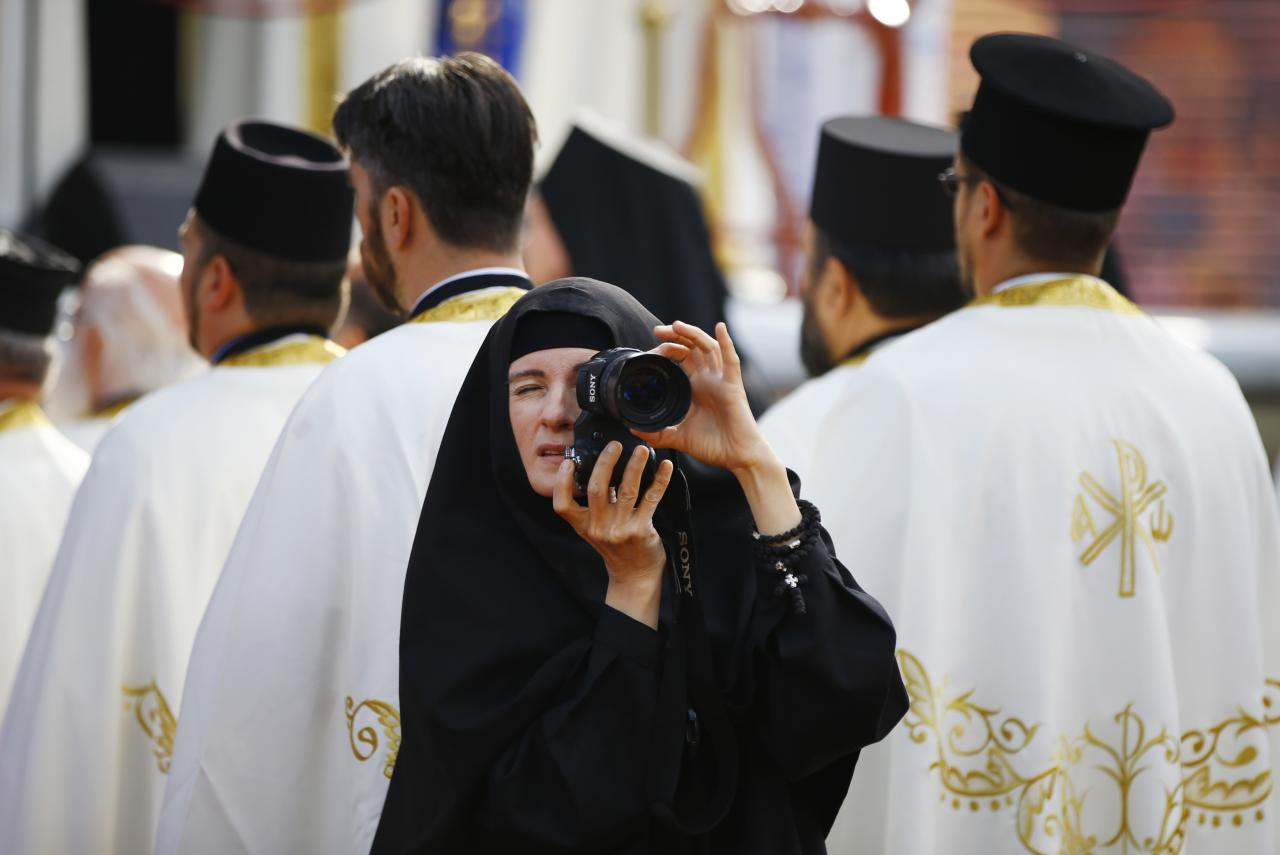 A nun takes pictures as believers mark 1,700 years since the Edict of Milan, when Roman emperor Constantine issued instructions to end the persecution of Christians, in the southern Serbian city of Nis October 6, 2013. Nis, some 220 km (137 miles) south of Belgrade, is the birthplace of Constantine the Great, the first Roman emperor to convert to Christianity. The Edict of Milan, which he had a part in enacting, proclaimed official tolerance of Christianity across the Empire. REUTERS/Marko Djurica (SERBIA - Tags: RELIGION SOCIETY ANNIVERSARY TPX IMAGES OF THE DAY)