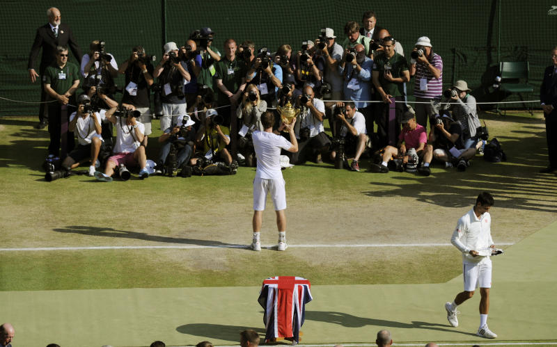 Andy Murray of Britain, center, poses for photographers with the trophy after defeating Novak Djokovic of Serbia, right, in the Men's singles final match at the All England Lawn Tennis Championships in Wimbledon, London, Sunday, July 7, 2013. (AP Photo/Tom Hevezi, Pool)