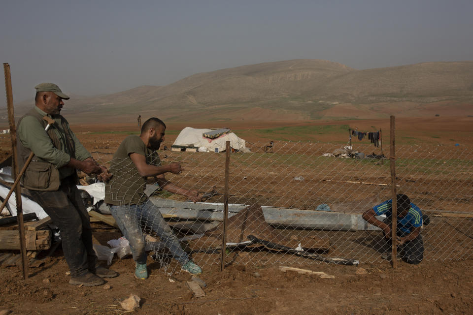 Palestinian Bedouins boy rebuild a fence for an animal pen after Israeli troops demolished tents and other structures of the Khirbet Humsu hamlet in the Jordan Valley in the West Bank, Wednesday, Feb. 3, 2021. A battle of wills is underway in the occupied West Bank, where Israel has demolished the herding community of Khirbet Humsu three times in as many months, displacing dozens of Palestinians. Each time they have returned and tried to rebuild, saying they have nowhere else to go. (AP Photo/Maya Alleruzzo)