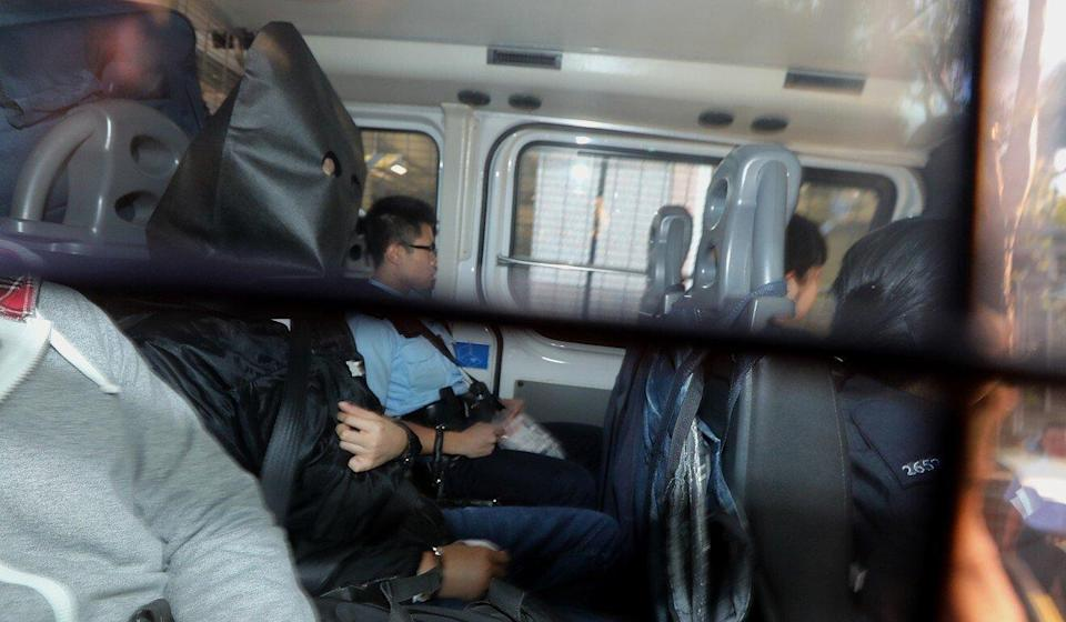 Tung Pak-fai (hooded) is taken to court just days after his knife attack on lawmaker Junius Ho. Photo: Felix Wong