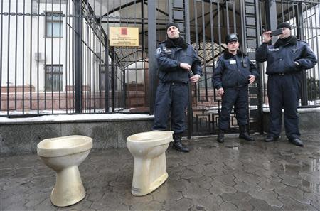 """Policemen stand guard as activists of the """"Democratic Alliance"""" movement stage a performance during a protest rally in front of the Russian embassy in Kiev, February 7, 2014. REUTERS/Konstantin Chernichkin"""