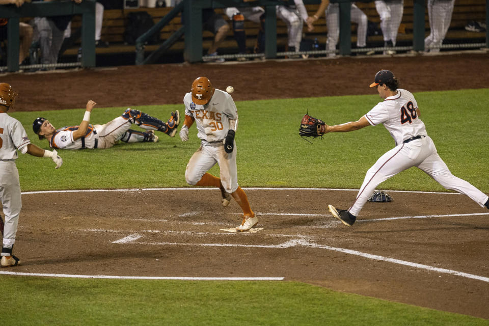Texas outfielder Eric Kennedy (30) runs home on a wild pitch by Virginia pitcher Mike Vasil (48) during a baseball game in the College World Series Thursday, June 24, 2021, at TD Ameritrade Park in Omaha, Neb. (AP Photo/John Peterson)